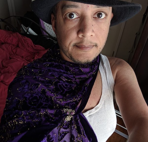 Pax with black hat, white tank top, and purple cape