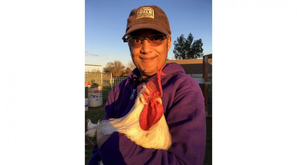 The author poses holding Ricky, a rooster, at PreetiRang Sanctuary. Pax is wearing a purple hoodie, tinted eyeglasses, and a faded black AIDS Walk San Francisco 2000 baseball cap. Photo by Ziggy, November 2016.